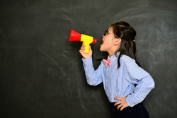 attractive happy little girl teacher using loudspeaker tool talking and shouting when she standing in front of blackboard background.