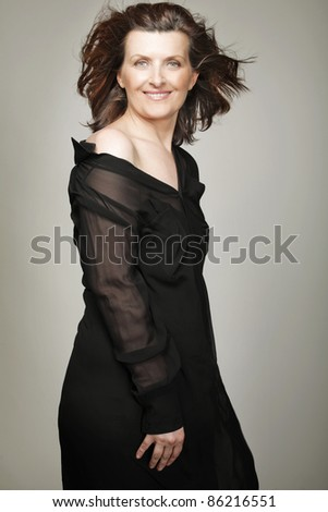 Attractive happy middle-aged woman in black dress.