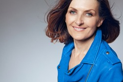 Attractive happy middle-aged woman in blue jacket.