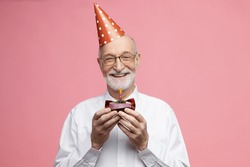 Attractive happy retired Caucasian male wearing bow tie, glasses and cone hat celebrating his 80th anniversary, posing isolated with birthday cake in his hands, going to blow out candle and make wish