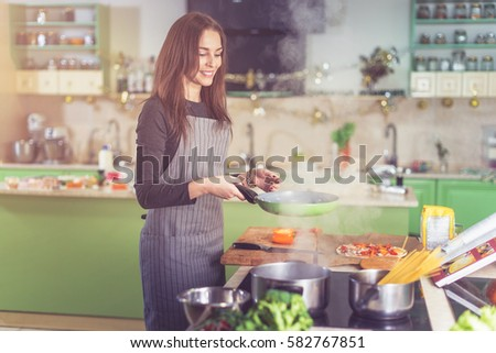 Attractive happy slim Caucasian female cooking pasta, making sauce using a pan at home.