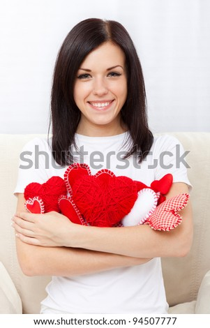 Attractive happy smiling brunette young girl holding lot of red valentine heart, woman sitting on couch at home, concept of valentine's day love