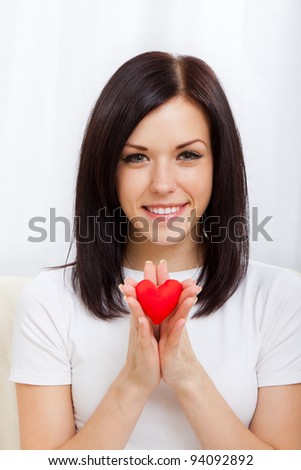 Attractive happy smiling brunette young girl holding one little red valentine heart, woman sitting on couch at home, concept of valentine's day