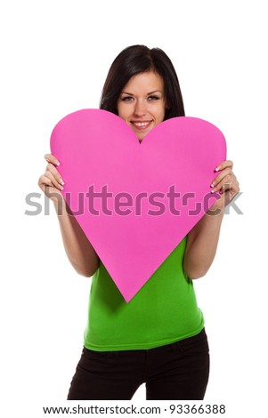 Attractive happy smiling brunette young girl holding pink valentine heart; isolated on white background, concept of valentine's day