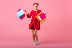 attractive happy smiling stylish woman shopaholic in red trendy dress holding colorful shopping bags on pink studio background isolated, sale excited, fashion trend on saint valentine's day