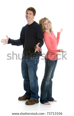 Attractive happy teenage couple standing back to back in studio with white background