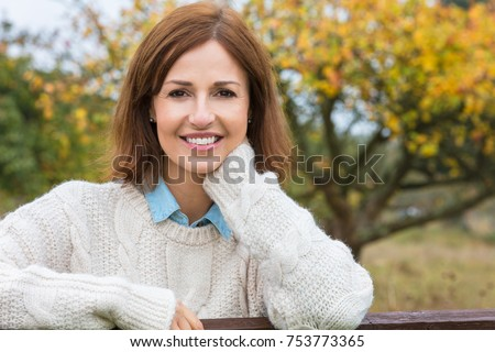 Attractive happy thoughtful middle aged woman leaning resting on fence in the countryside
