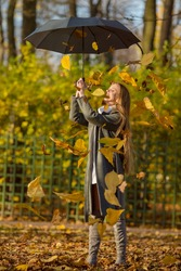 Attractive happy woman in a gray coat holds an umbrella in her hands. Leaf fall in the autumn park. Beautiful young woman is walking among the falling leaves. Yellow foliage. Fall season. Autumn mood.