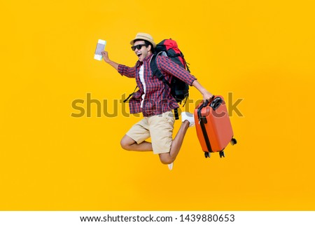 Attractive happy young Asian man tourist with air ticket and passport in his hand jumping isolated on yellow studio background
