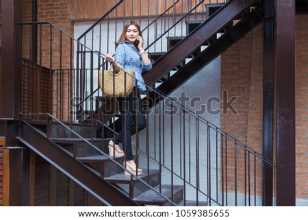 Attractive happy young asian woman going shopping walking down the stairs of a shopping plaza while talking to her smart phone
