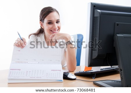 Attractive happy young businesswoman behind her desk. Checking her schedule. - stock photo