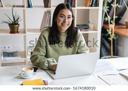 Attractive happy young girl student studying at the college library, sitting at the desk, using laptop computer