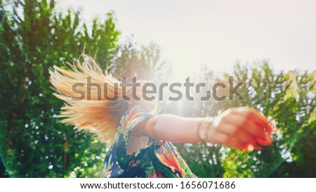 Attractive happy young woman in white t shirt flying hair enjoying her free time at sunset outdoor. Beauty blonde girl portrait at summer. Freedom lifestyle freedom concept. Sun glow on background