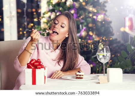 Attractive happy young woman sitting and eating desser. New Year eve celebrating concept