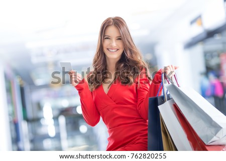 Attractive happy young woman with credit card and shopping bags.