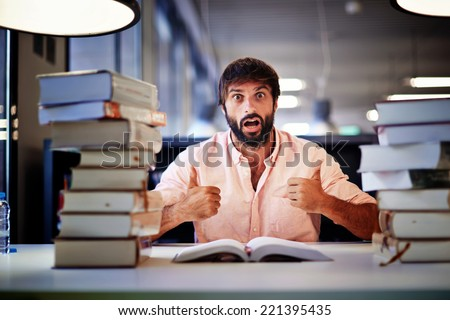 Attractive high school student ready for his final exam, surprise emotion face of student sitting at the library desk with two pile of books,student with two thumbs up make positive facial expressions