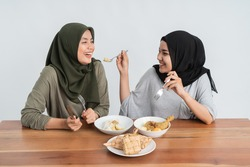 attractive hijab woman breakfasting eating some ketupat or rice cake dish
