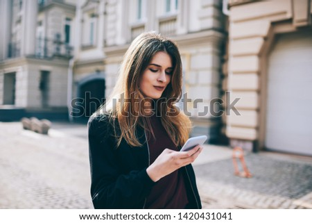 Attractive hipster girl outdoors  check mail by new cellular , woman sending text messages on modern mobile phone, female tourist searching news about places of  interest online walking on street #1420431041