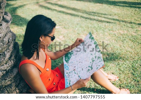 Attractive hipster girl resting on green grass in summer city park and learning information from paper map for choosing popular monuments and explore it, concept of travelling and discovering #1407797555