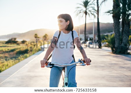Attractive hipster millennial woman or teenager in blue american denim and simple white tshirt rides bicycle on sunset promenade next to beach, authentic tattoos  #725633158