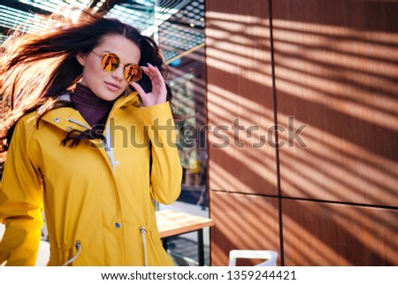 Attractive hipster young woman in stylish sunglasses in a stylish yellow coat