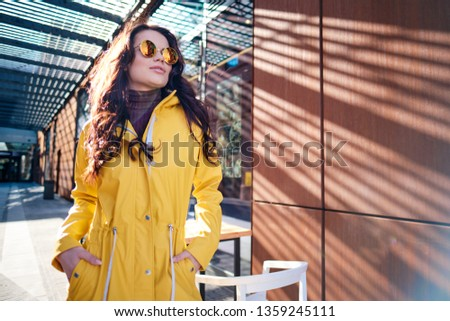 Attractive hipster young woman in stylish sunglasses in a stylish yellow coat #1359245111