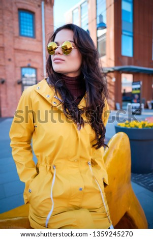 Attractive hipster young woman in stylish sunglasses in a stylish yellow coat #1359245270