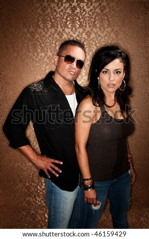 Attractive Hispanic Couple Posing in Front of Gold Background