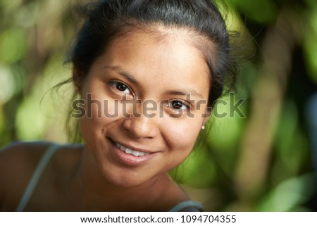 Attractive hispanic girl portrait close-up on blurred natural nbackground #1094704355