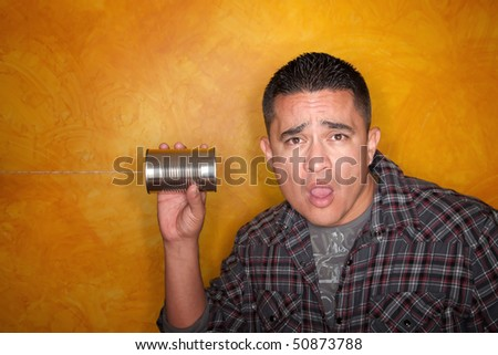 Attractive Hispanic man with tin can telephone