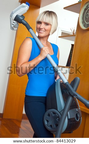 attractive housewife holding vacuum cleaner in her home