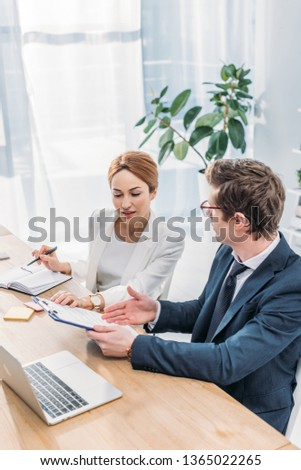 attractive hr looking at clipboard near coworker in glasses  #1365022265