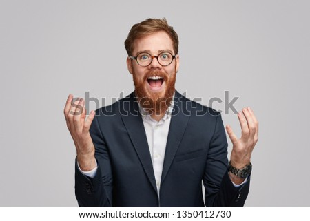 Attractive Irish businessman with ginger beard gesturing with hands and yelling in amazement isolated on gray background