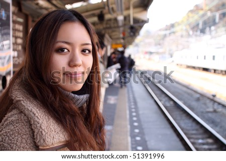 Attractive Japanese girl standing and waiting in a train station