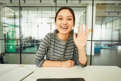 Attractive lady greeting somebody with a wave and smile