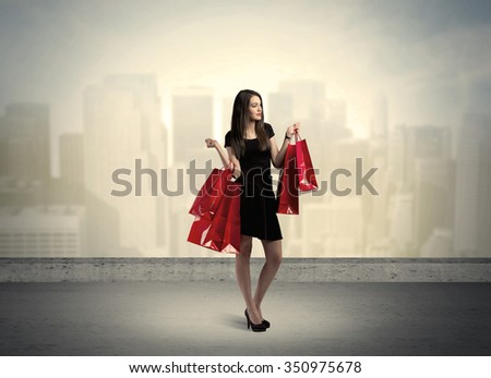 Attractive lady in black holding red shopping bags standing in front o urban landscape with tall buildings concept #350975678
