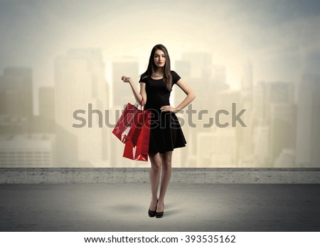 Attractive lady in black holding red shopping bags standing in front o urban landscape with tall buildings concept #393535162