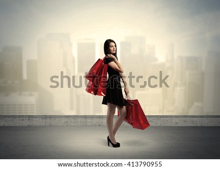 Attractive lady in black holding red shopping bags standing in front o urban landscape with tall buildings concept #413790955