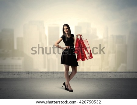 Attractive lady in black holding red shopping bags standing in front o urban landscape with tall buildings concept #420750532