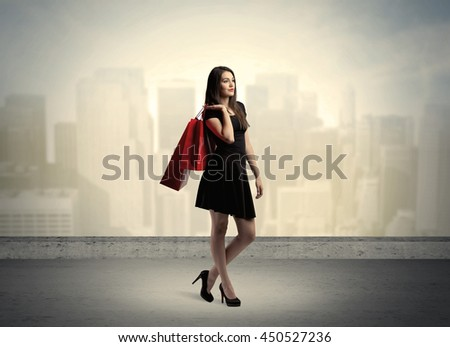 Attractive lady in black holding red shopping bags standing in front o urban landscape with tall buildings concept #450527236