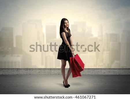 Attractive lady in black holding red shopping bags standing in front o urban landscape with tall buildings concept #461067271