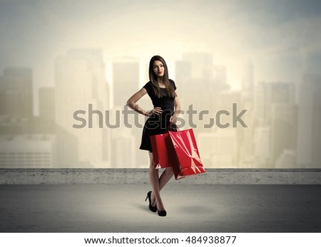 Attractive lady in black holding red shopping bags standing in front o urban landscape with tall buildings concept #484938877