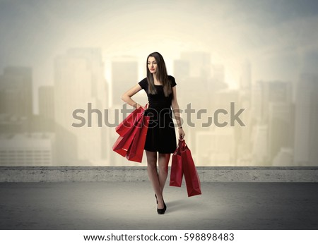 Attractive lady in black holding red shopping bags standing in front o urban landscape with tall buildings concept #598898483