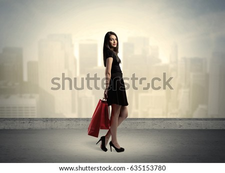 Attractive lady in black holding red shopping bags standing in front o urban landscape with tall buildings concept #635153780