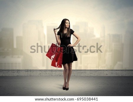 Attractive lady in black holding red shopping bags standing in front o urban landscape with tall buildings concept #695038441