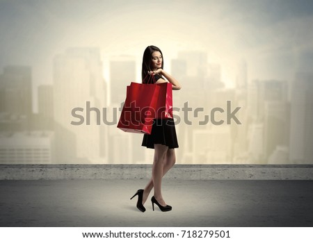 Attractive lady in black holding red shopping bags standing in front o urban landscape with tall buildings concept #718279501