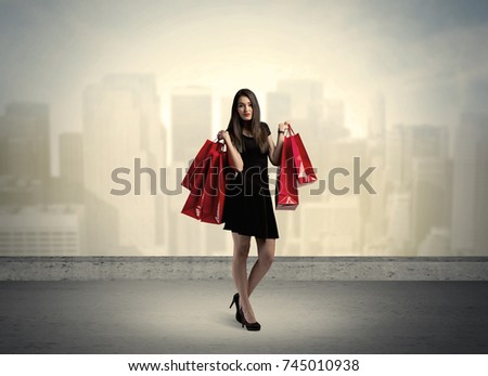 Attractive lady in black holding red shopping bags standing in front o urban landscape with tall buildings concept #745010938
