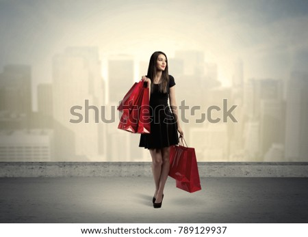 Attractive lady in black holding red shopping bags standing in front o urban landscape with tall buildings concept #789129937