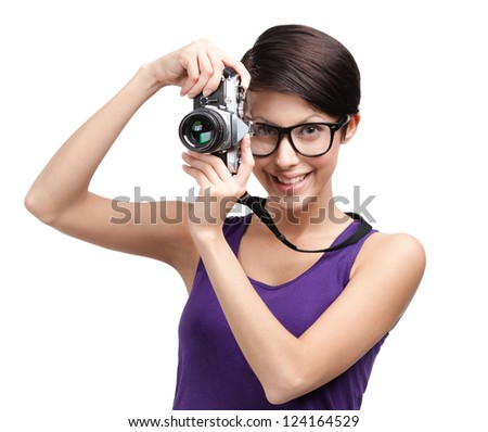 Attractive lady in spectacles hands retro photographic camera, isolated on white
