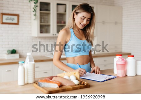 Attractive lady taking notes and standing near kitchen table with meat, dairy products and food supplements on it Stock fotó ©